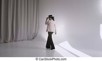 Pretty woman in black trousers and a hat poses in a light ...