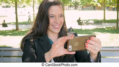Pretty woman in business suit using smart phone for video...