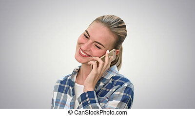 Pretty woman in casual clothes talking on the phone and smiling on white background.