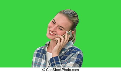 Pretty woman in casual clothes talking on the phone and smiling on a Green Screen, Chroma Key.