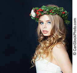 Pretty woman in Christmas crown on black background