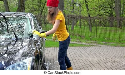 Pretty woman in colorful clothes washing black automobile car with soapy sponge.