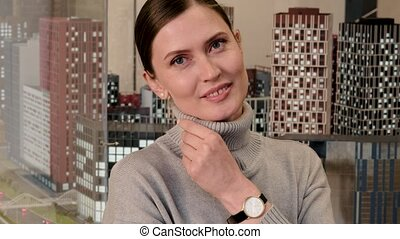 Pretty positive young woman wearing grey cowl neck sweater with wristwatch poses for camera against models of skyscrapers in room