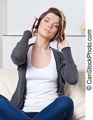 Pretty woman in earphones listens to music