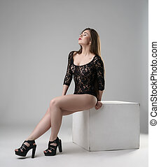 Pretty woman in erotic bodysuit sitting on cube