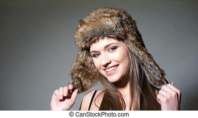 Pretty woman in fur hat - Closeup portrait of pretty young...