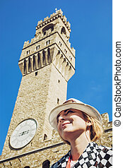 Pretty woman in hat is posing under the Palazzo Vecchio in the city Florence