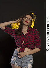 Pretty woman in jeans shorts and red checked shirt