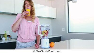 Pretty woman in kitchen drinking orange juice beside juicer...
