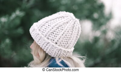Pretty woman in knitted hat turns around with beautiful smile on winter forest background. Young girl with perfect make-up and feminine hairstyle. Slow motion. High quality 4k footage