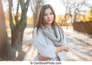 Pretty woman in knitted sweater on the background of autumn park