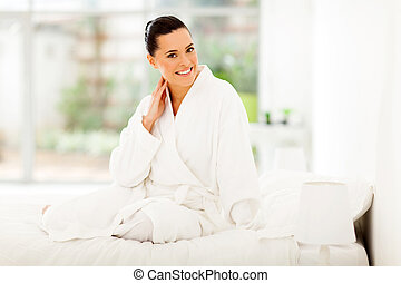 pretty woman in pajamas sitting on bed