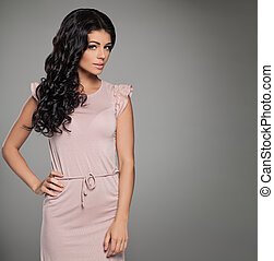 Pretty Woman in Pink Summer Dress on Background with Copy space. Fashion Portrait