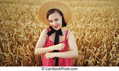 Pretty woman in red dress and straw hat funny dancing in...