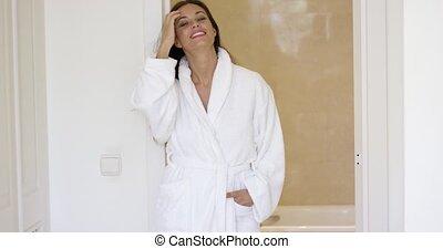 Pretty woman in robe adjusting hair