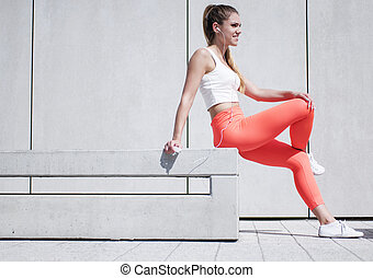 Pretty Woman in Sports Attire Sitting on the Bench