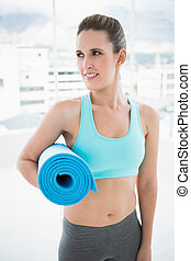 Pretty woman in sportswear holding exercise mat