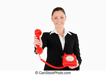 Pretty woman in suit holding a red telephone