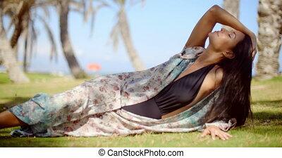 Pretty Woman in Summer Dress Resting on Grassy