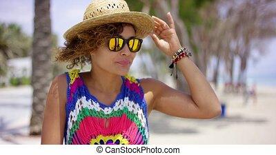 Pretty woman in sunglasses adjusting hat - Pretty adult...