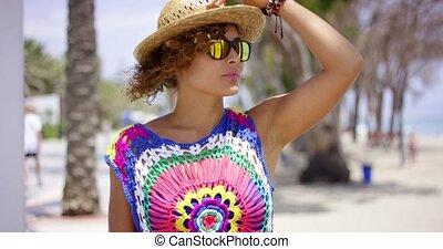 Pretty woman in sunglasses adjusting hat