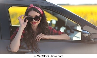 Pretty woman in sunglasses looking out of the car