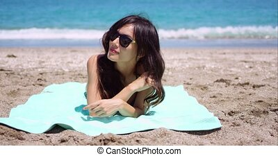 Pretty woman in sunglasses sunbathing on a beach