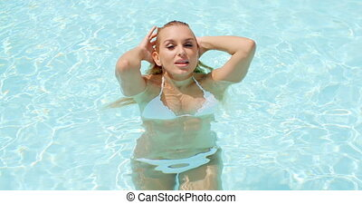 Pretty Woman in the Pool Holding Back her Wet Hair