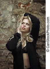 Pretty woman in unbuttoned shirt near the rocks