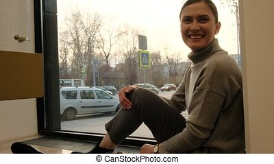Pretty smiling young woman in grey warm sweater poses for camera sitting on windowsill against city street outside light room