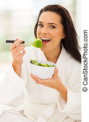 woman in white bathrobe eating salad