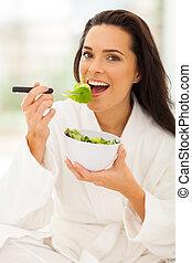 woman in white bathrobe eating salad - pretty woman in white...
