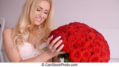 Pretty Woman in White Bra Touching a Rose Bouquet