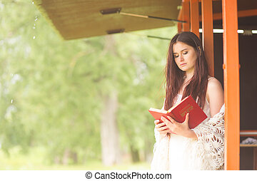 Pretty woman in white dress read book. Girl sits on the terrace