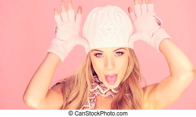 Attractive young blonde woman wearing winter outfit, head and shoulders portrait on pink.
