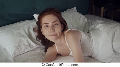 Pretty redhead woman inviting to come and lying on bed.