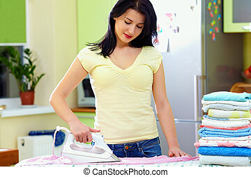 pretty woman ironing clothes at home