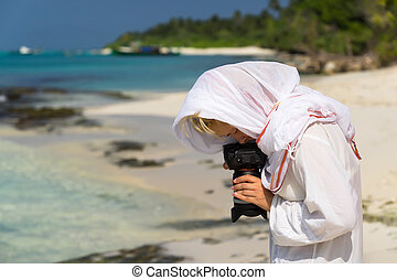 Pretty woman is a photographer with slr camera