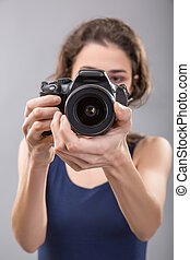 Pretty woman is a professional photographer with camera
