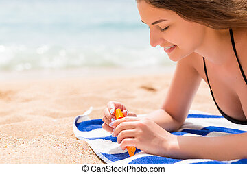Pretty woman is lying on the towel at the beach and opening a tube of sun cream to protect her skin from sunburn