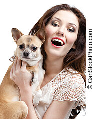 Pretty woman keeps on the hands a straw-colored small dog