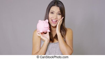 Pretty woman kissing her pink piggy bank - Pretty young...