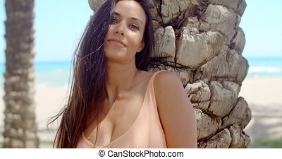 Pretty Woman Leaning Against Beach Palm Tree Trunk