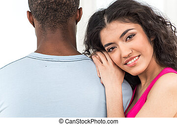 pretty woman leaning on man shoulder and smiling on white background. African man standing with his back to camera