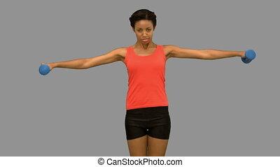 Pretty woman lifting dumbbells on g