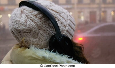 Pretty woman listening music in headphones on smartphone riding train, beautifull girl rides a city bus, 4k.