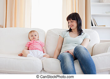 Pretty woman looking at her baby while sitting on a sofa