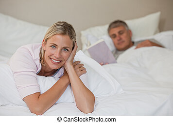 Pretty woman looking at the camera while her husband is sleeping
