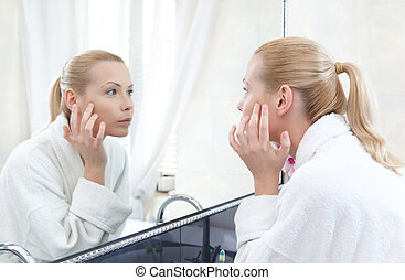 Pretty woman looks at her self in mirror