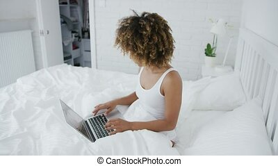 Pretty woman lounging on bed with laptop - Beautiful young...